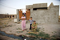 A family makes a new broom outside of their home at the Azadi IDP Camp in Iraq.