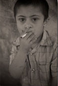 A six year old boy smokes cigarettes in the Moqoble Refugee Camp for Syrian Kurds in Iraq