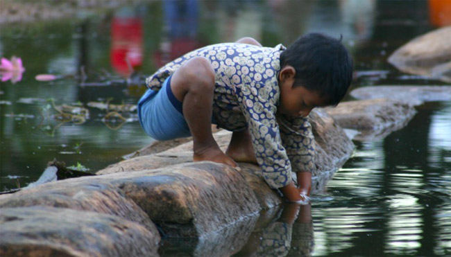A boy plays in the water outside of the temple in Angkor Wat