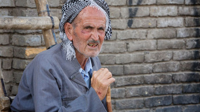 An old man sits on the street in Erbil, Iraq