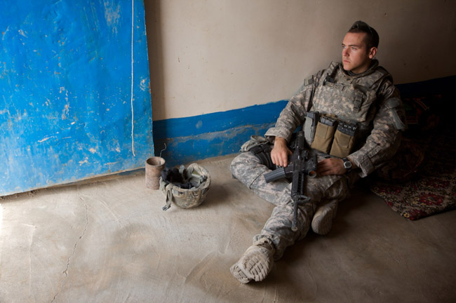 A soldier guards a doorway in a village outside of Kirkuk, Iraq
