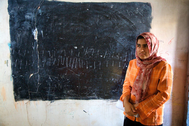 Tara Saifulla, 17, stands next to what was once a classroom's chalkboard.