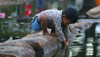 boy plays in the water outside of the temple in Angkor Wat